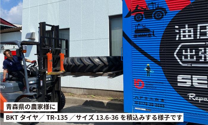 青森県の農家様にBKTトラクタータイヤTR-135 13.6-36をお届けする様子