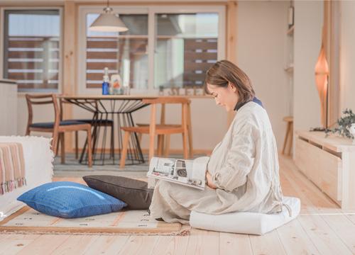 妊婦さんがマットレスに座って雑誌を読んでくつろいでいる写真