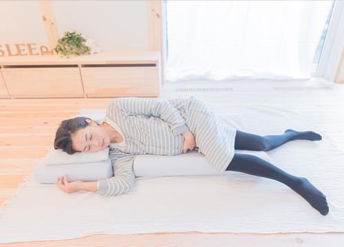 妊婦さんがマットレスの上に横たわっている写真