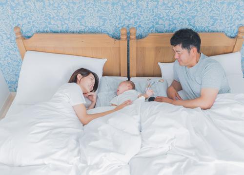 赤ちゃんを挟んで両親が添い寝している写真