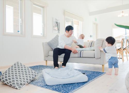 リビングで子供とお父さんが遊んでいる写真