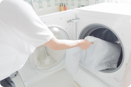 洗濯機へカバーを入れている写真